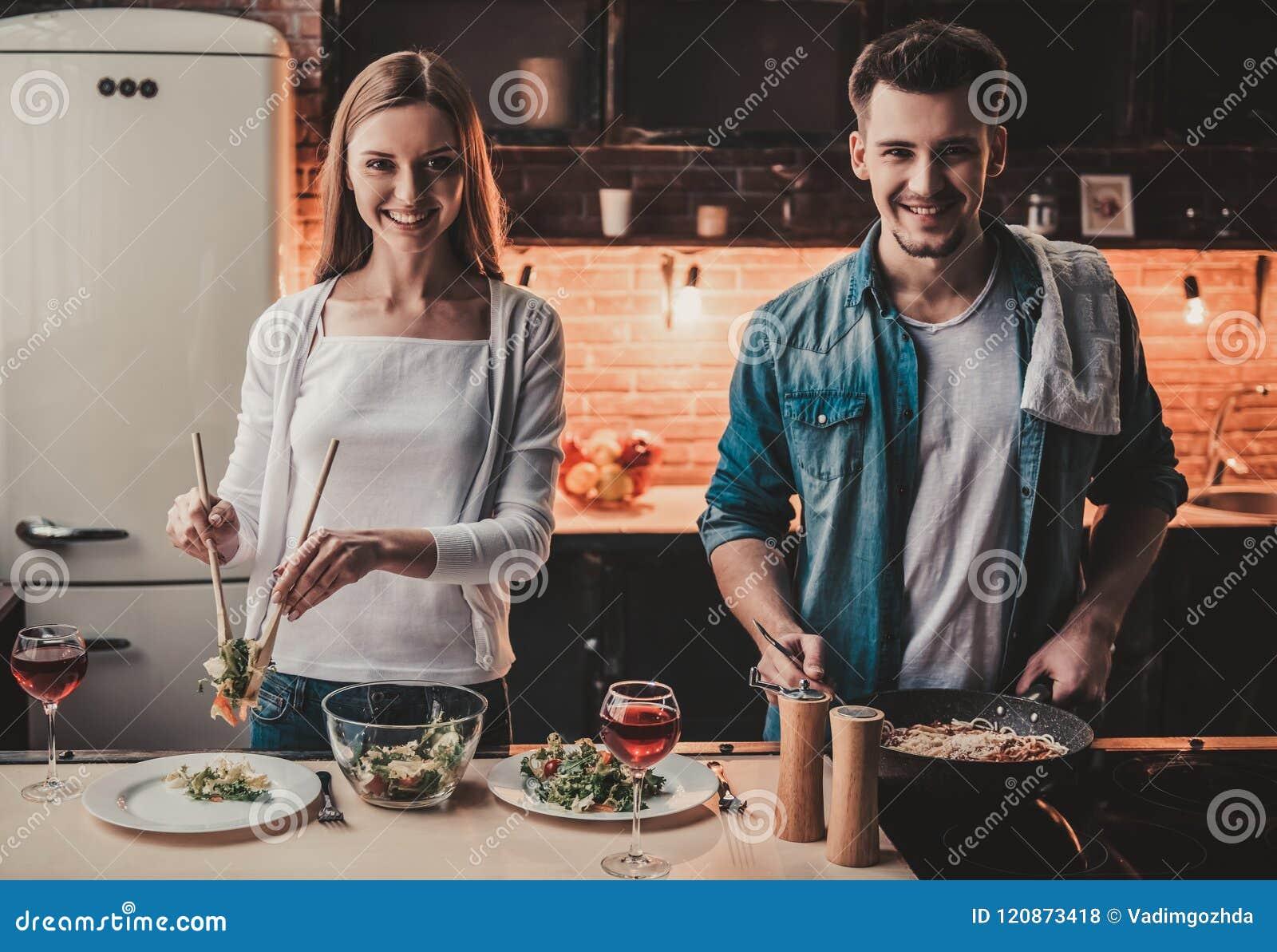 Молодые пары варя вино обедающего и питья красное