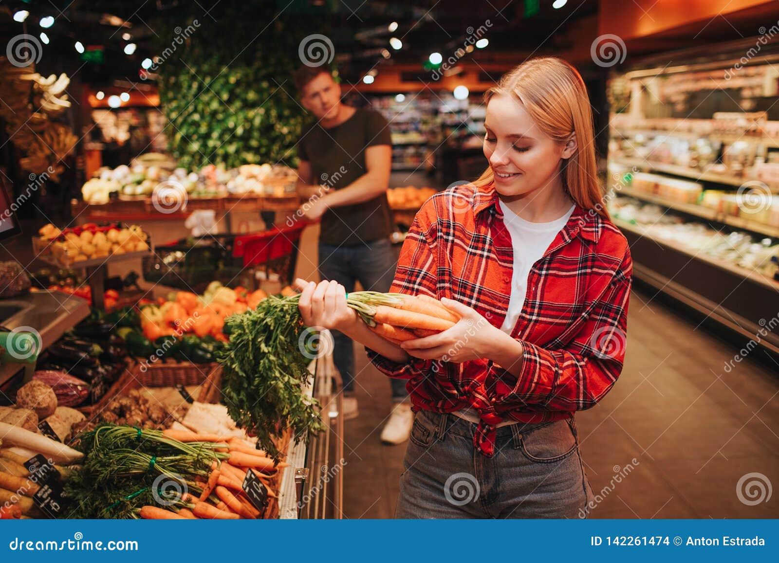 Молодые пары в гастрономе Стойка женщины в моркови фронта и владения в руках Она смотрит ее и улыбку Стойка молодого человека