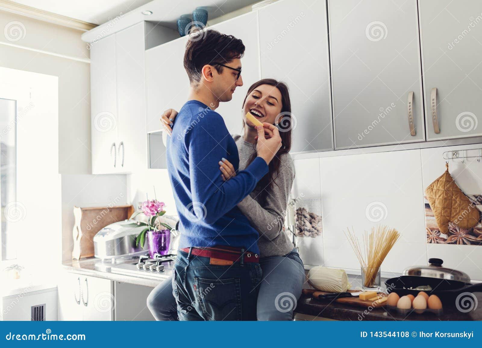 Молодые пары в кухне обнимая и есть сыр
