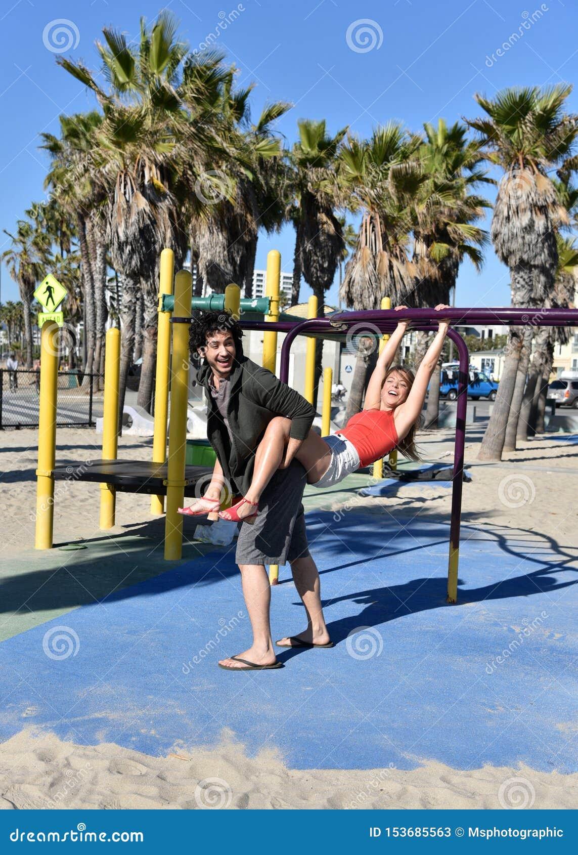 Молодые пары играя в спортивной площадке