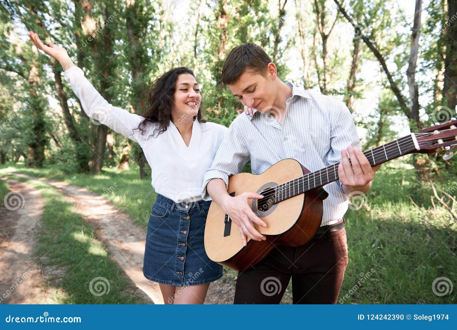 Молодые пары идя в лес, играющ гитару и танцы, природу лета, яркий солнечный свет, тени и зеленые листья, романтичные