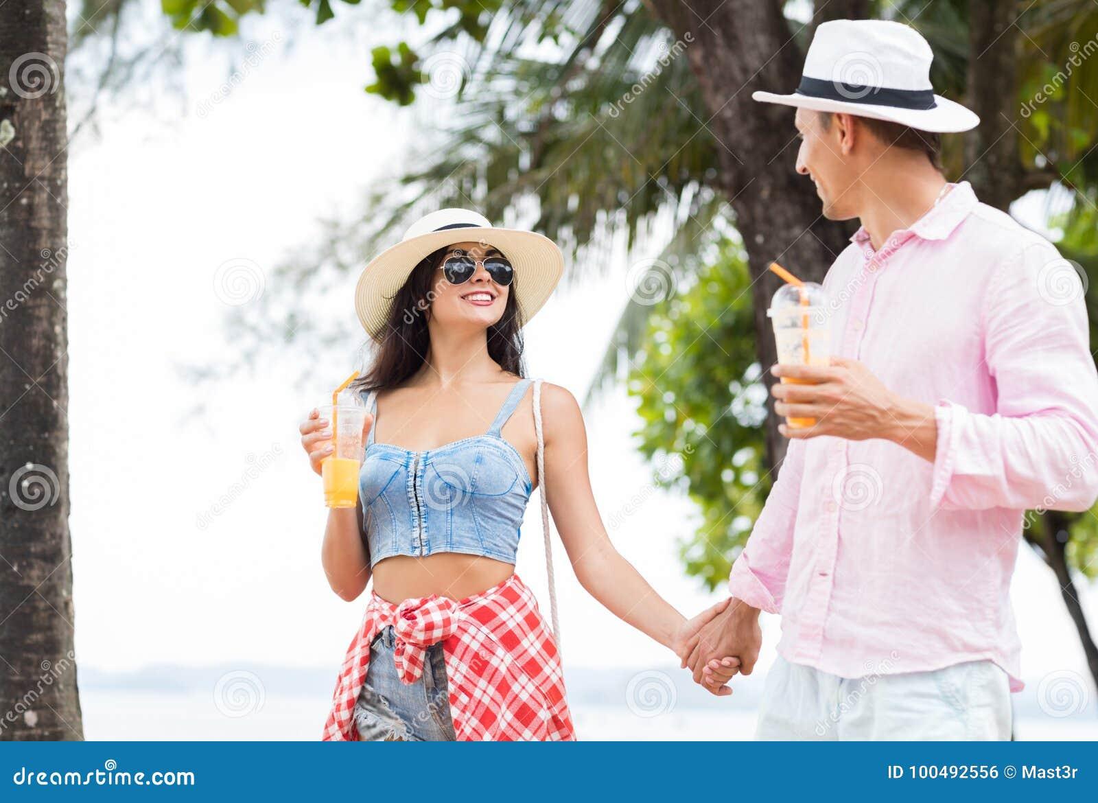 Молодые пары идя в парк на взморье держа руки счастливые туристы человека и женщины говоря на каникулах