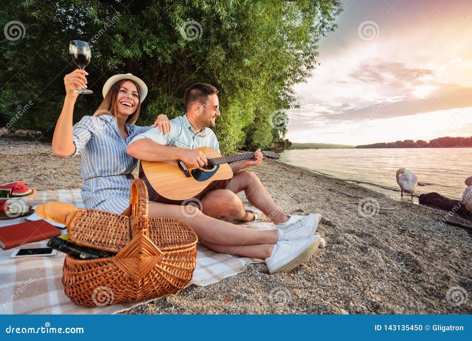 Молодые пары наслаждаясь их временем, имеющ романтичный пикник на пляже гитара играя петь