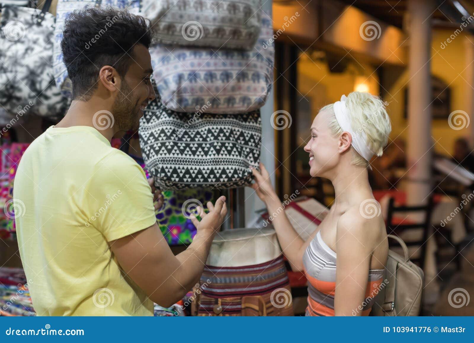 Молодые пары на покупках выбирая усмехаться сумки, человека и женщины счастливый в магазине розничной торговли