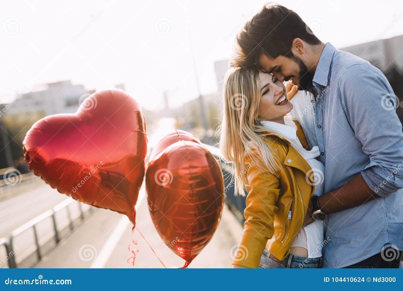 Молодые пары обнимая датировка и целовать внешний