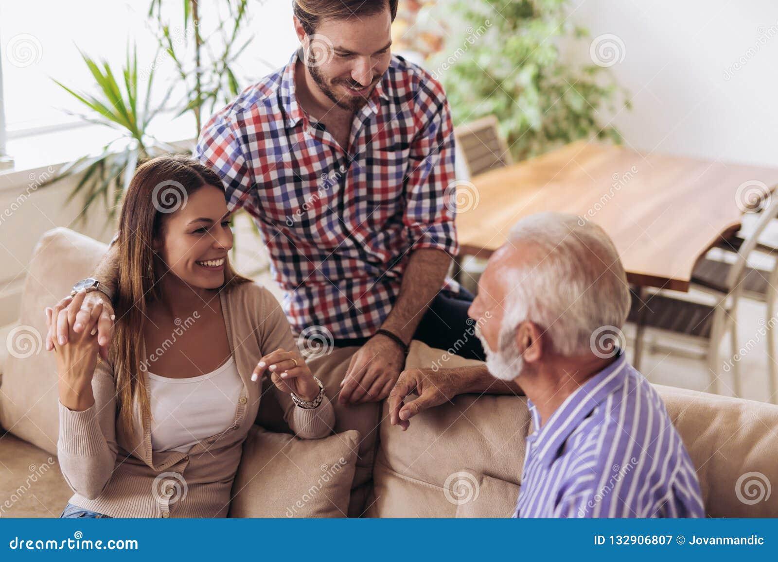 Молодые пары разговаривая с их старшим отцом