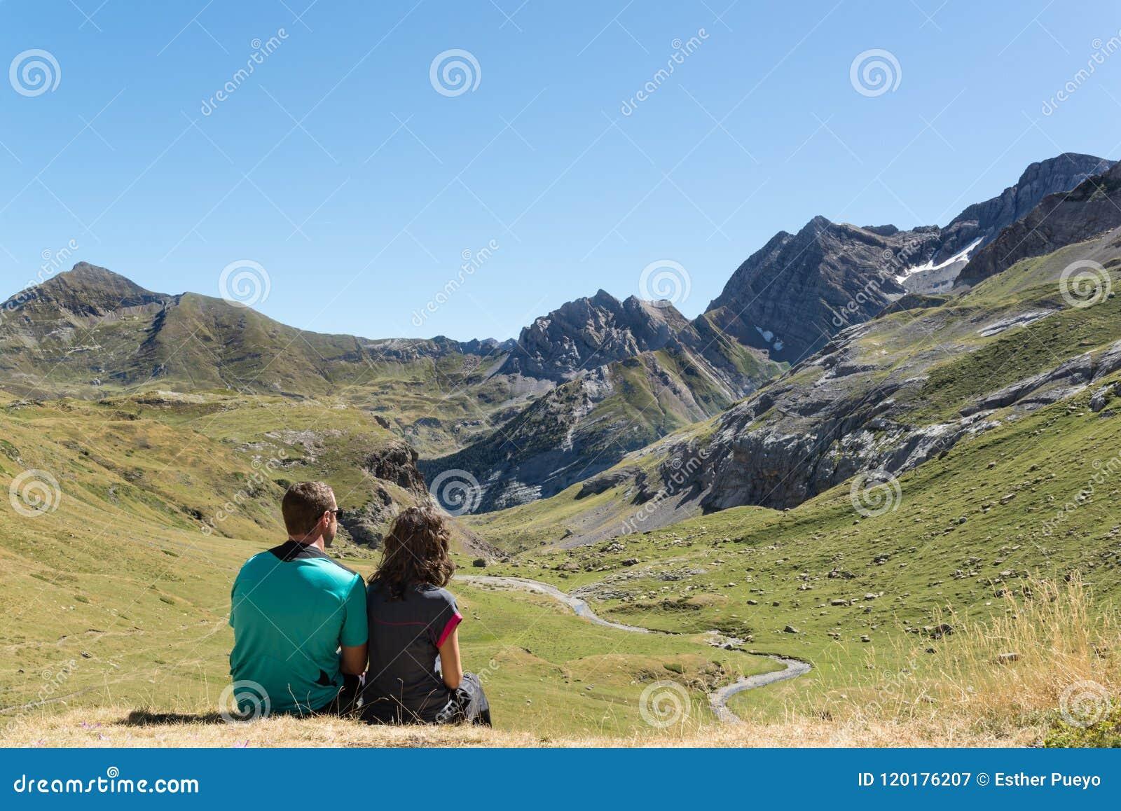 Молодые пары сидя вниз и смотря долина в Пиренеи