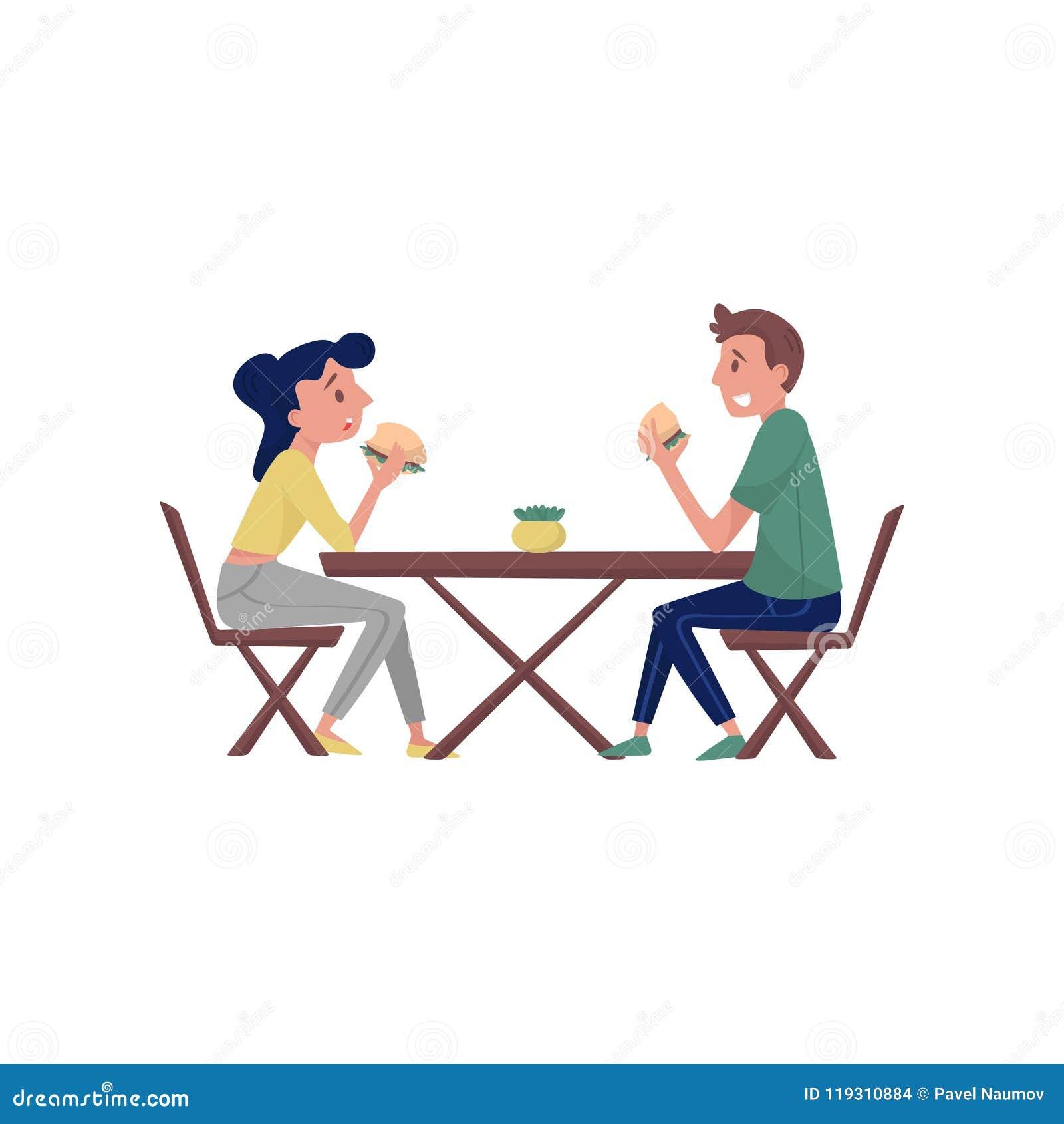 Молодые пары сидя за деревянным столом и есть вкусные бургеры обед гинеи предпосылки смешной над белизной времени портрета свиньи