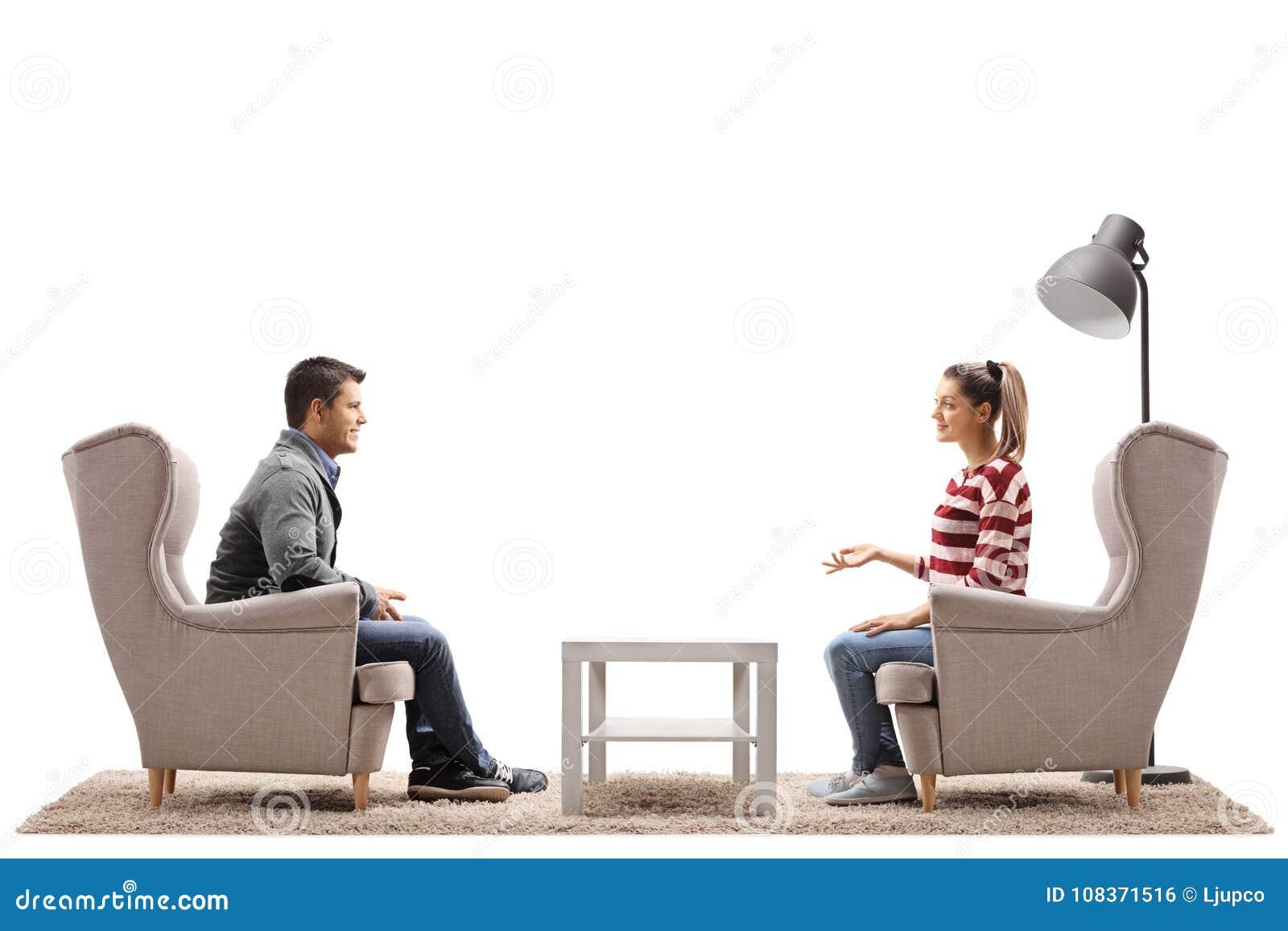 Молодые пары усаженные в кресла имея переговор