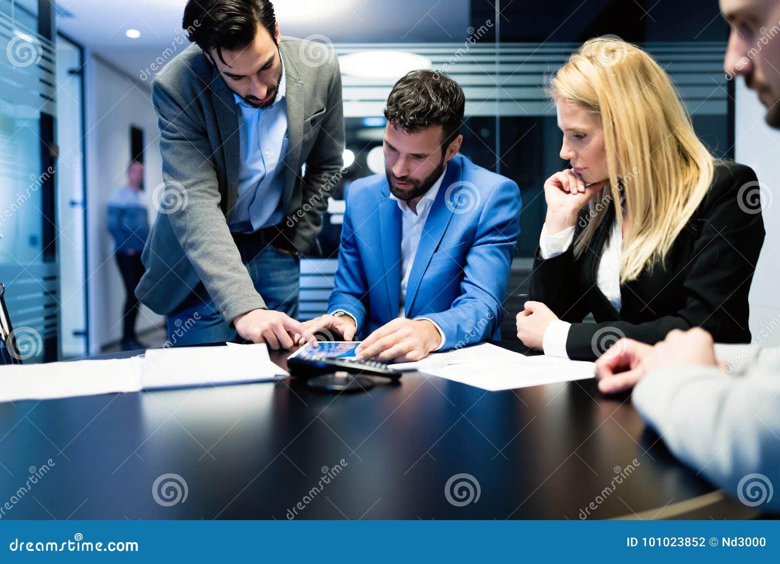 Молодые предприниматели работая на компьютере в офисе