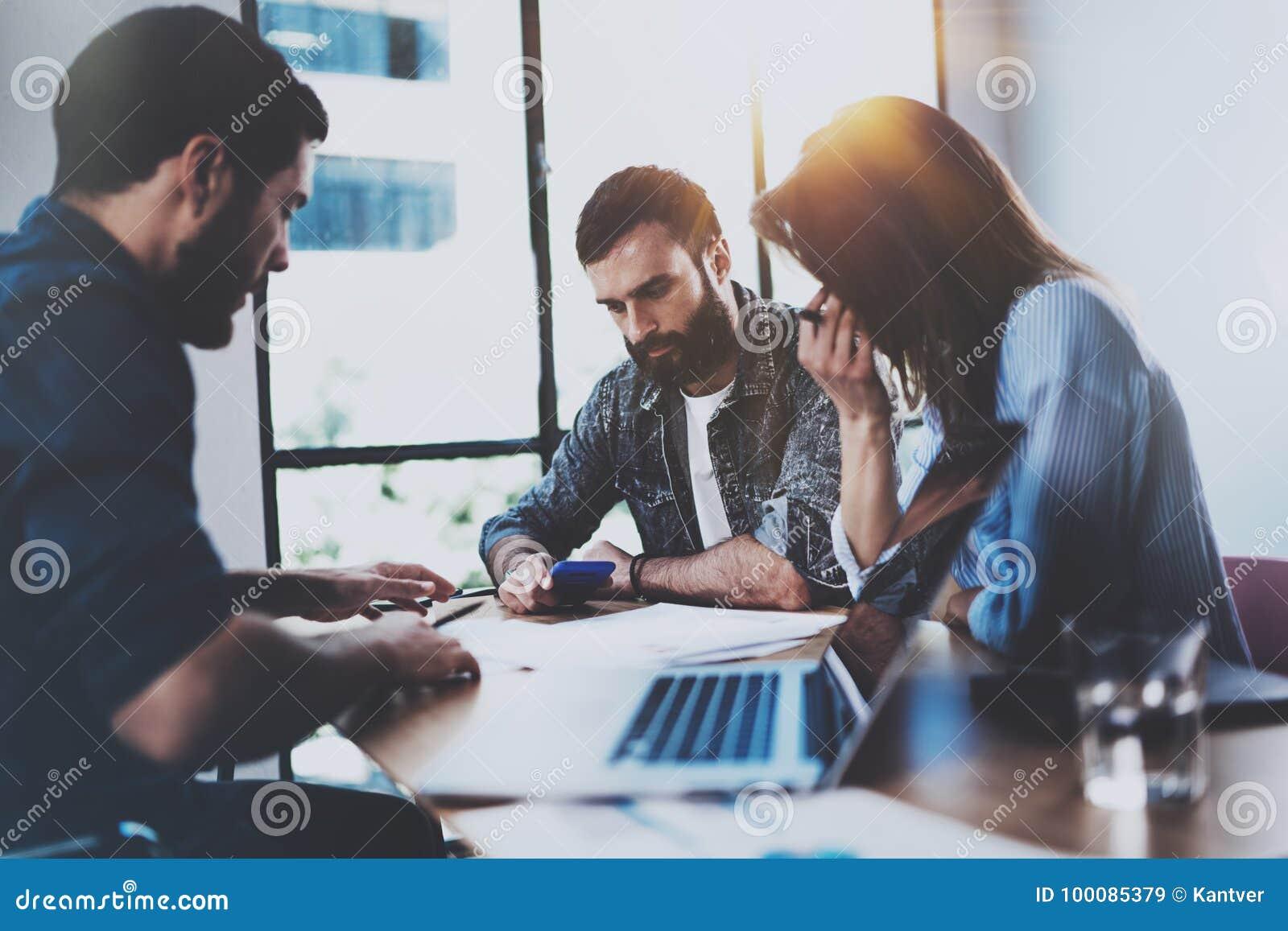 Молодые профессионалы дела обсуждая новое дело проектируют в современном офисе Группа в составе 3 сотрудника коллективно обсуждат