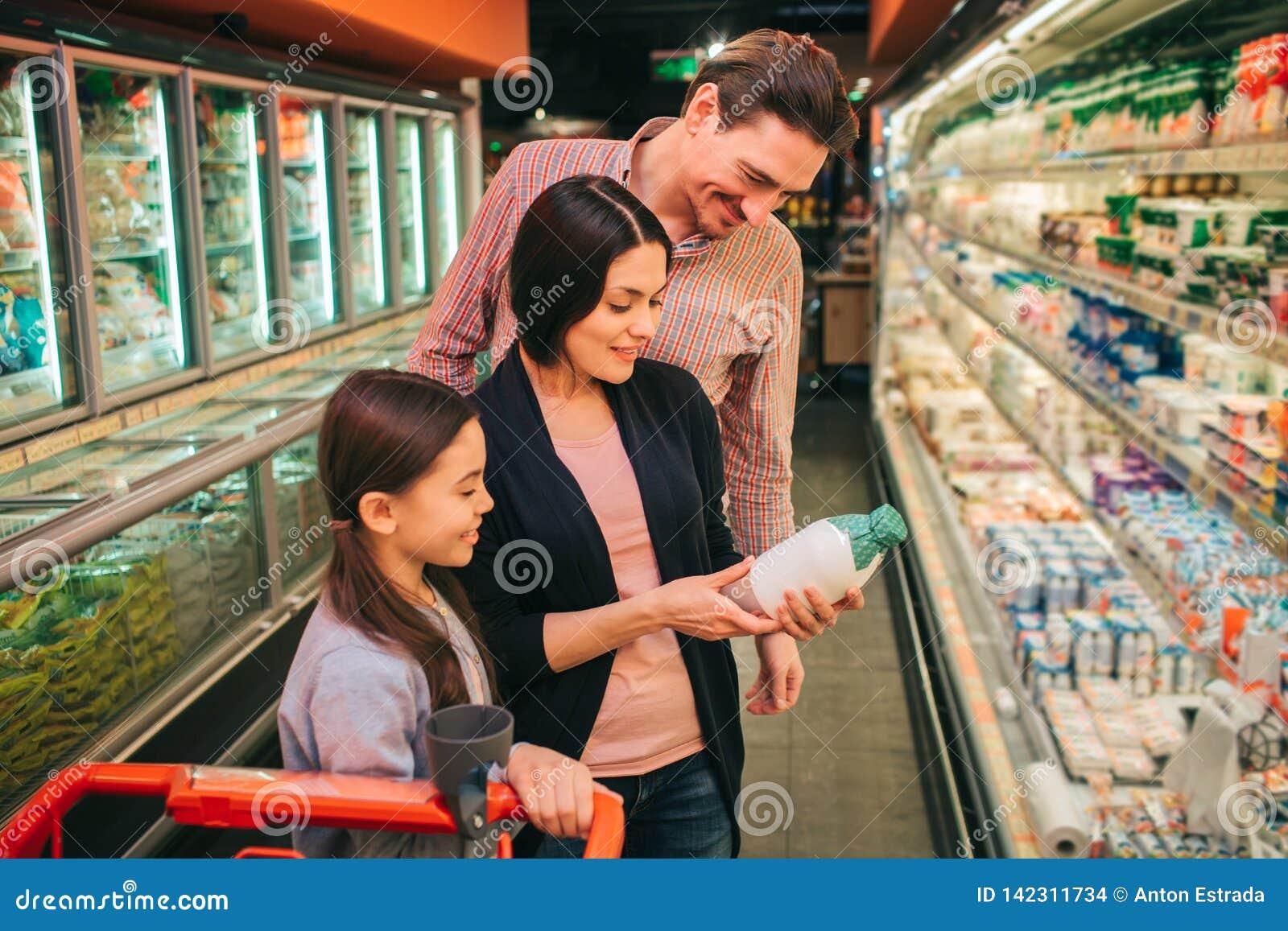Молодые родители и дочь в гастрономе Бутылка молока владением женщины и прочитать ингредиенты Стойка отца и дочери