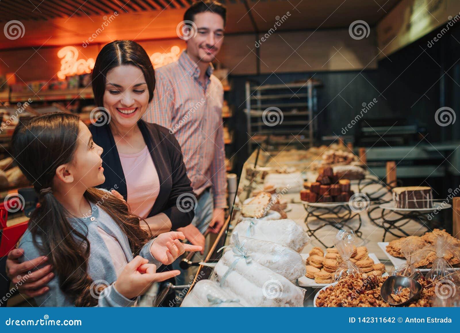 Молодые родители и дочь в гастрономе Взгляд девушки на матери со счастьем женщины женщины подростка милой усмешки персоны людей а