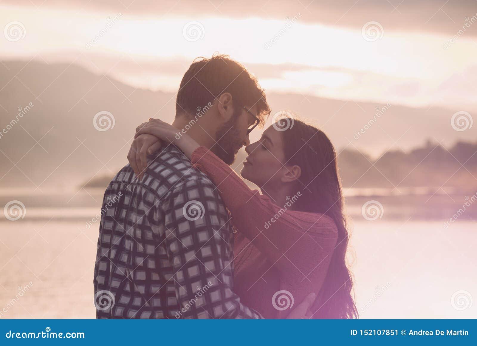 Молодые романтичные пары целуя на заходе солнца
