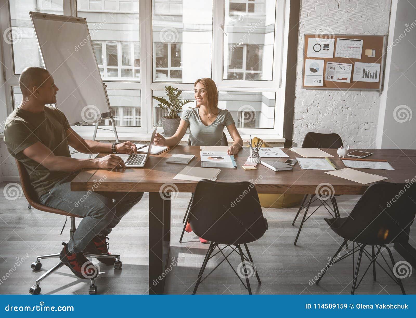 Молодые сотрудники наслаждаясь их рабочим днем