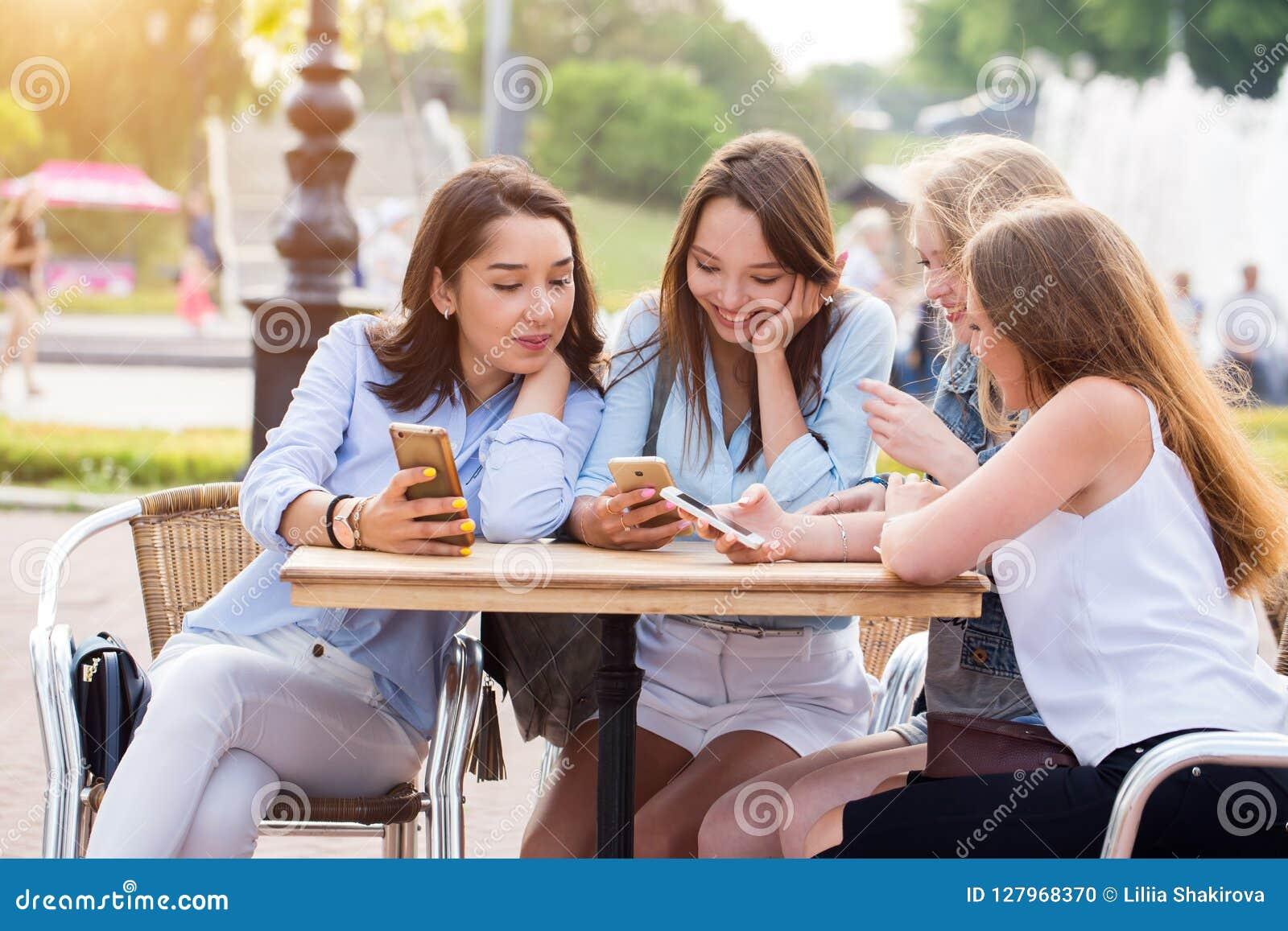 Молодые счастливые девушки студента используют smartphones в парке