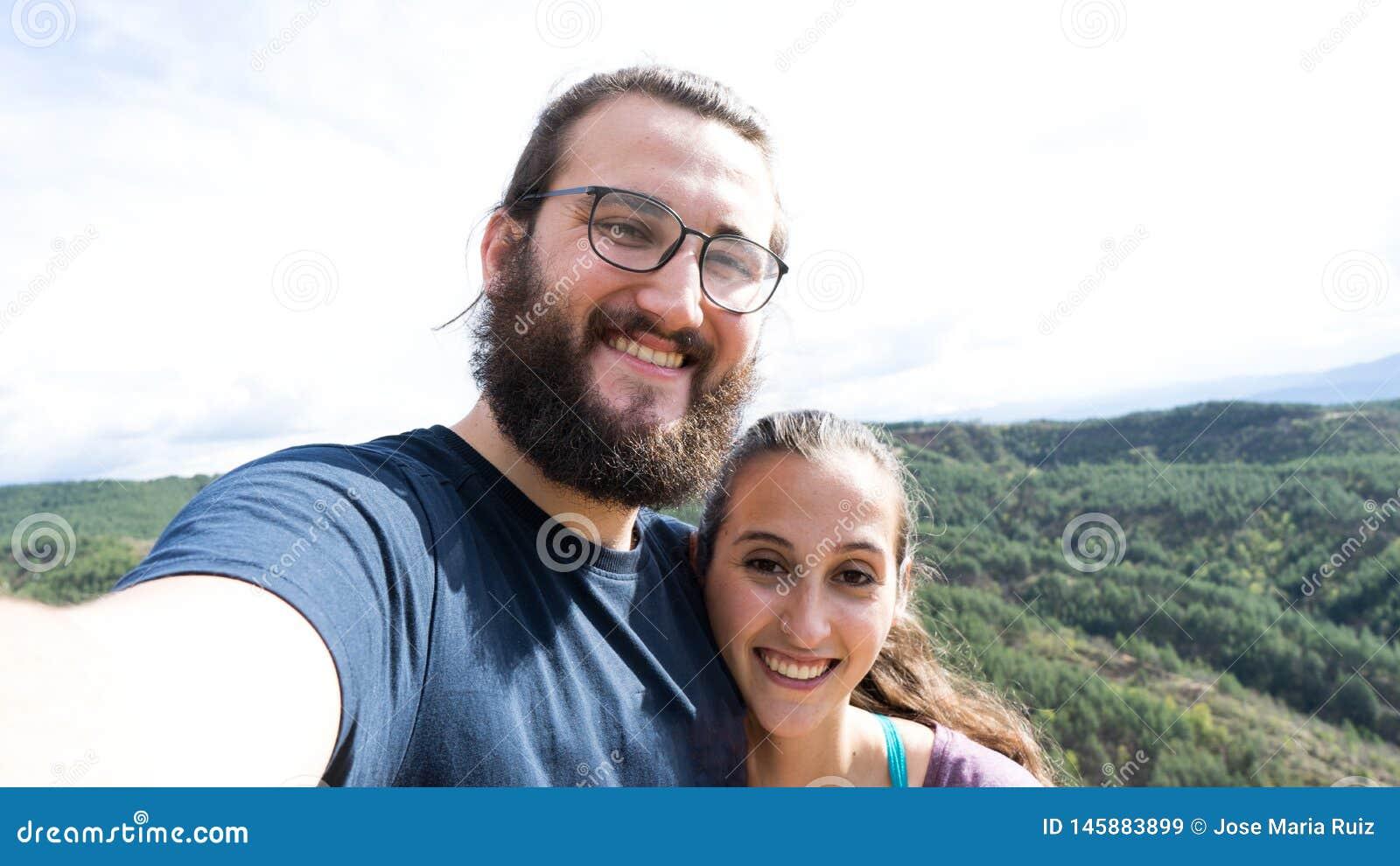 Молодые счастливые пары hiker принимая selfie в горе с умным телефоном
