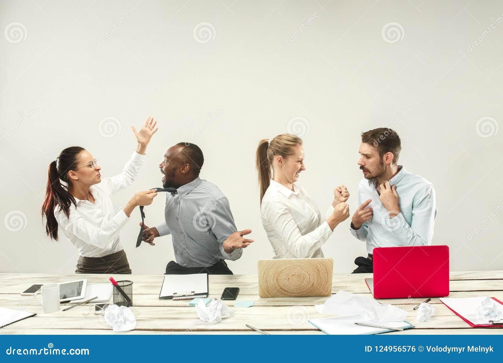 Молодые человеки и женщины сидя на офисе и работая на компьтер-книжках Концепция эмоций