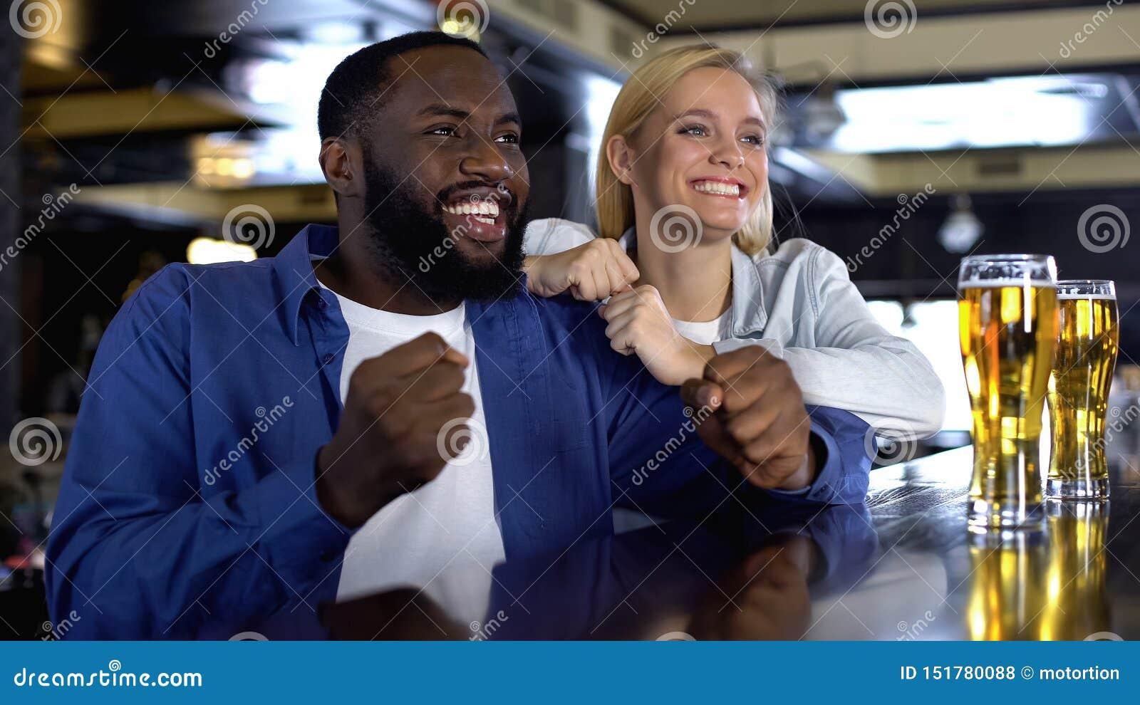 Молодые biracial пары укореняя любимую команду спорта в баре, наблюдая спичке онлайн