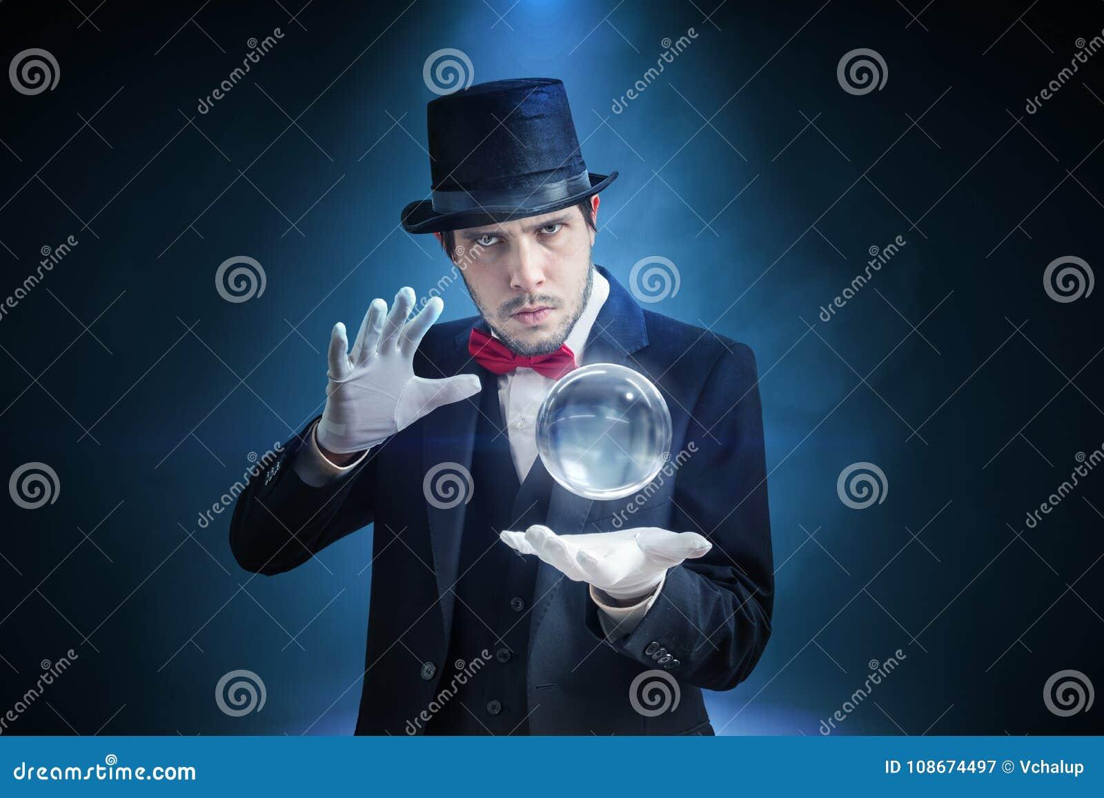 Молодые illusionist, волшебник или рассказчик удачи предсказывают будущее с кристаллической сферой
