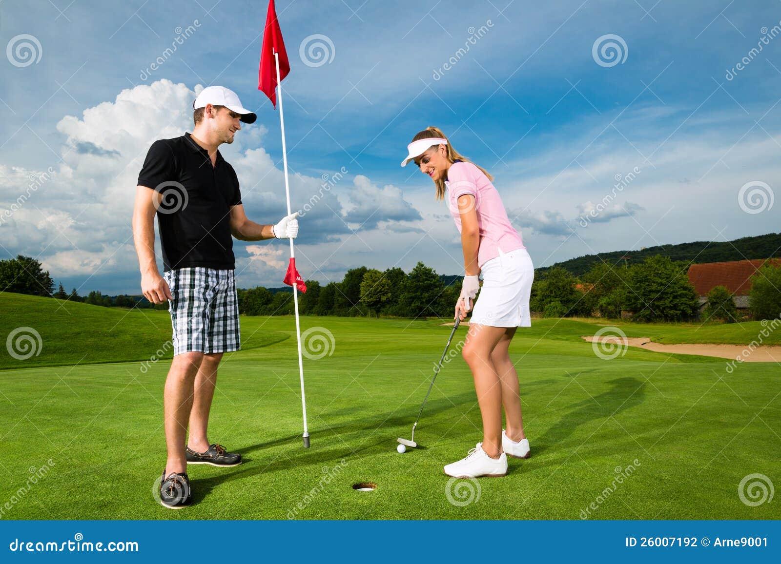Молодые sportive пары играя гольф на курсе