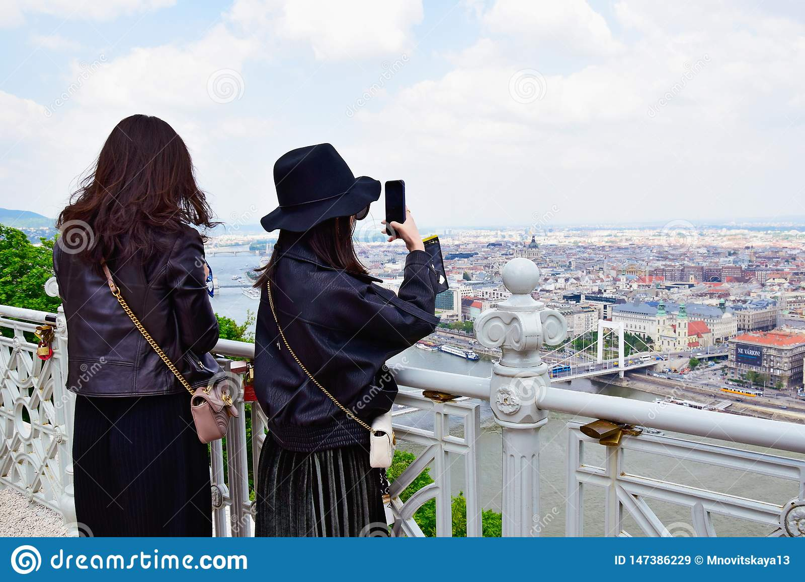 2 молодых азиатских женщины фотографируя сценарные взгляды Будапешта