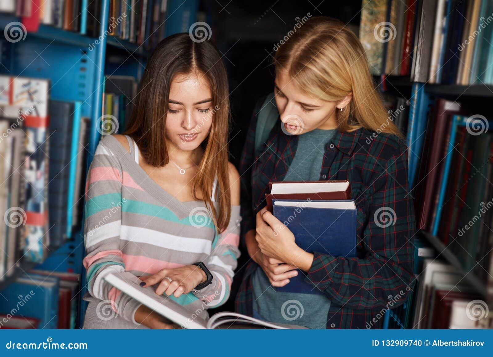 2 молодых книги shooses студенток на библиотеке