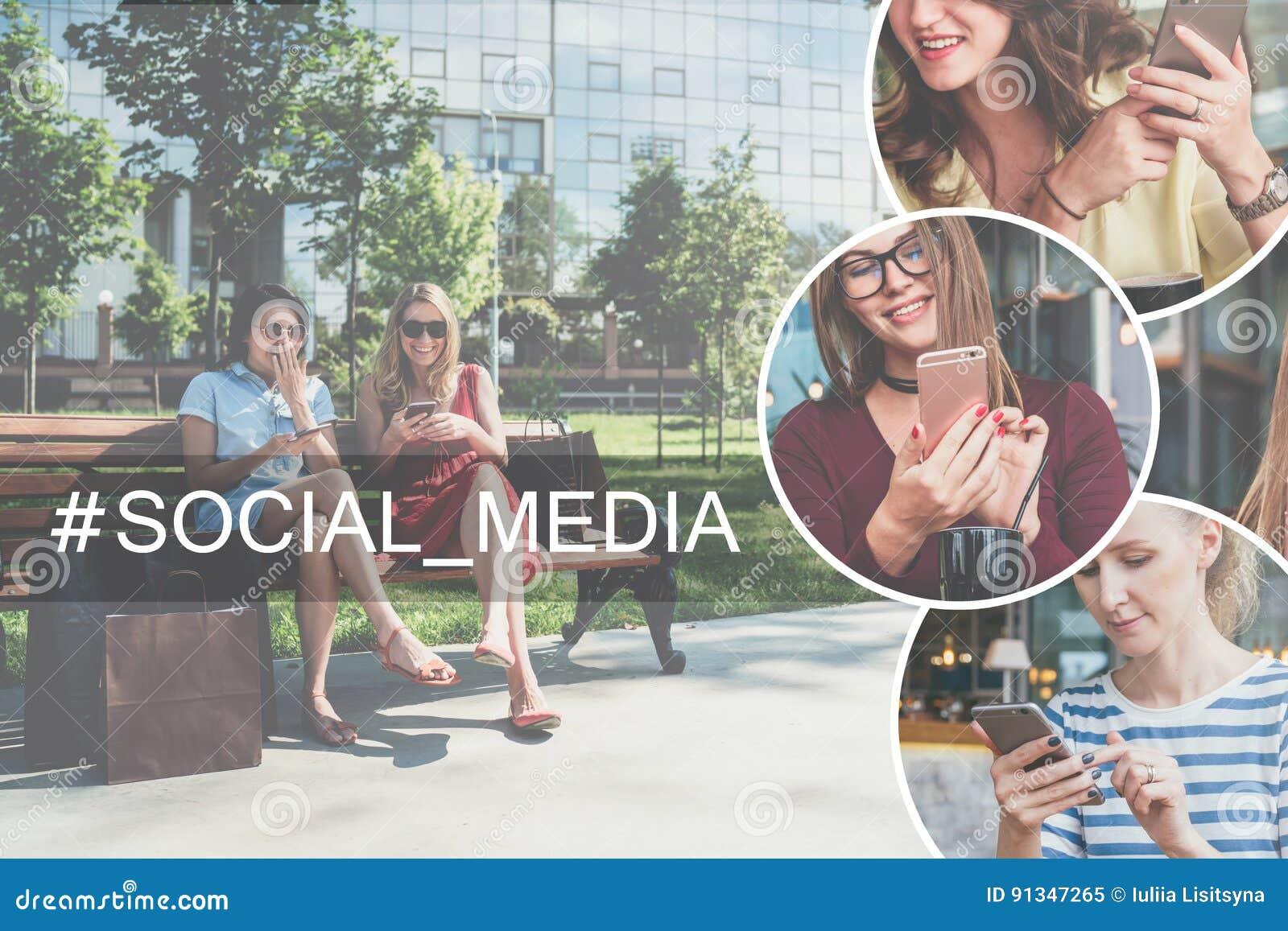 2 молодых смеясь над женщины в платьях сидя на скамейке в парке, остатках после ходить по магазинам и использования их smartphone
