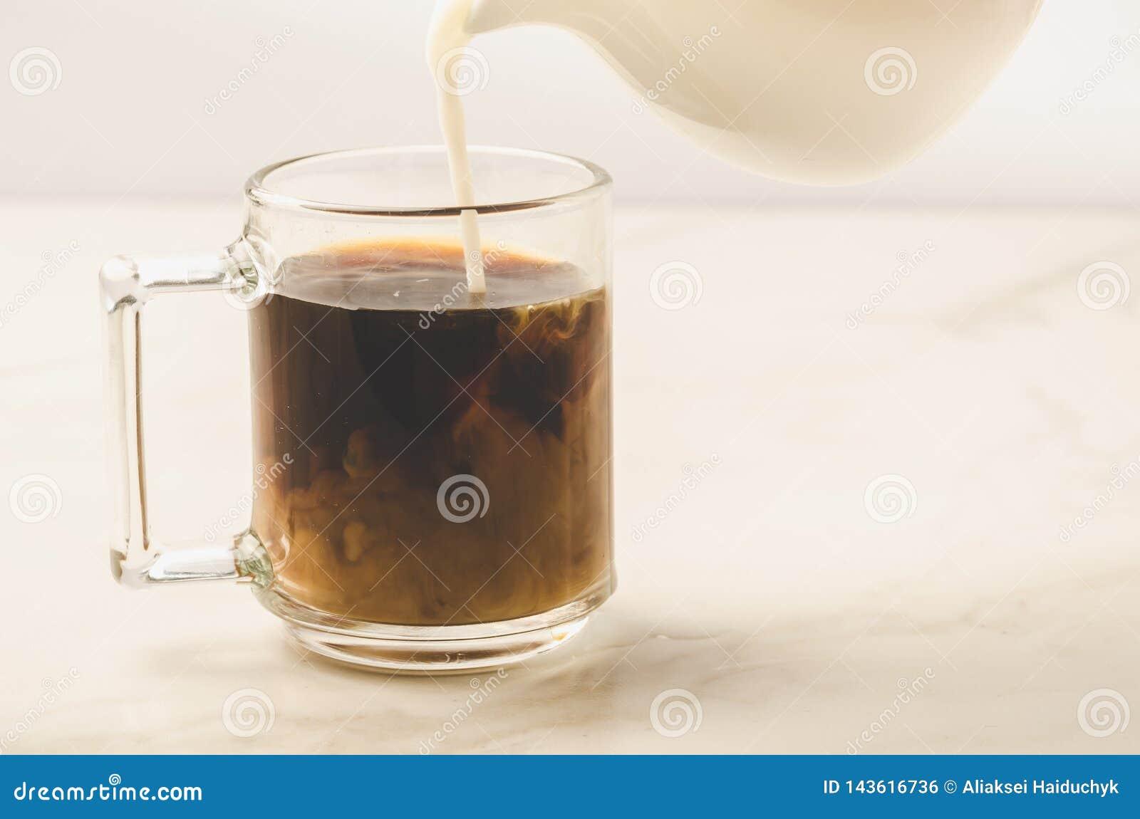 Молоко добавлено к стеклу кофе/молоку добавлено к стеклу кофе на белой мраморной предпосылке r