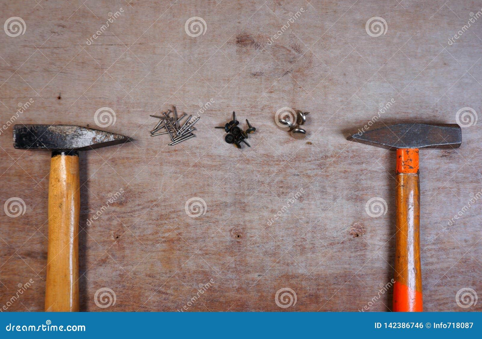 Молоток и ногти на деревянной предпосылке доски
