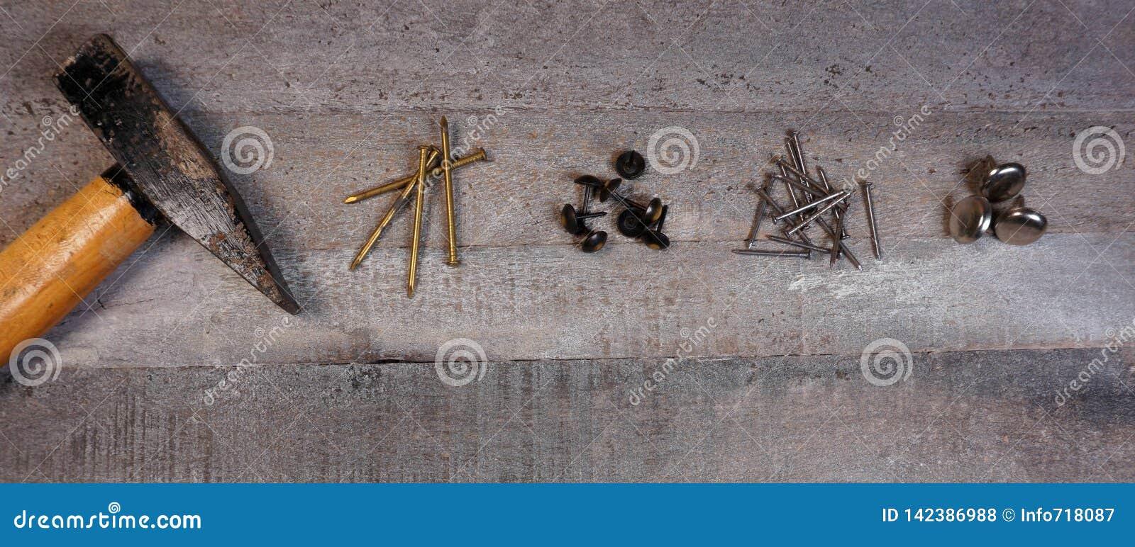 Молоток и ногти на естественной деревянной предпосылке с космосом экземпляра для вашего собственного текста