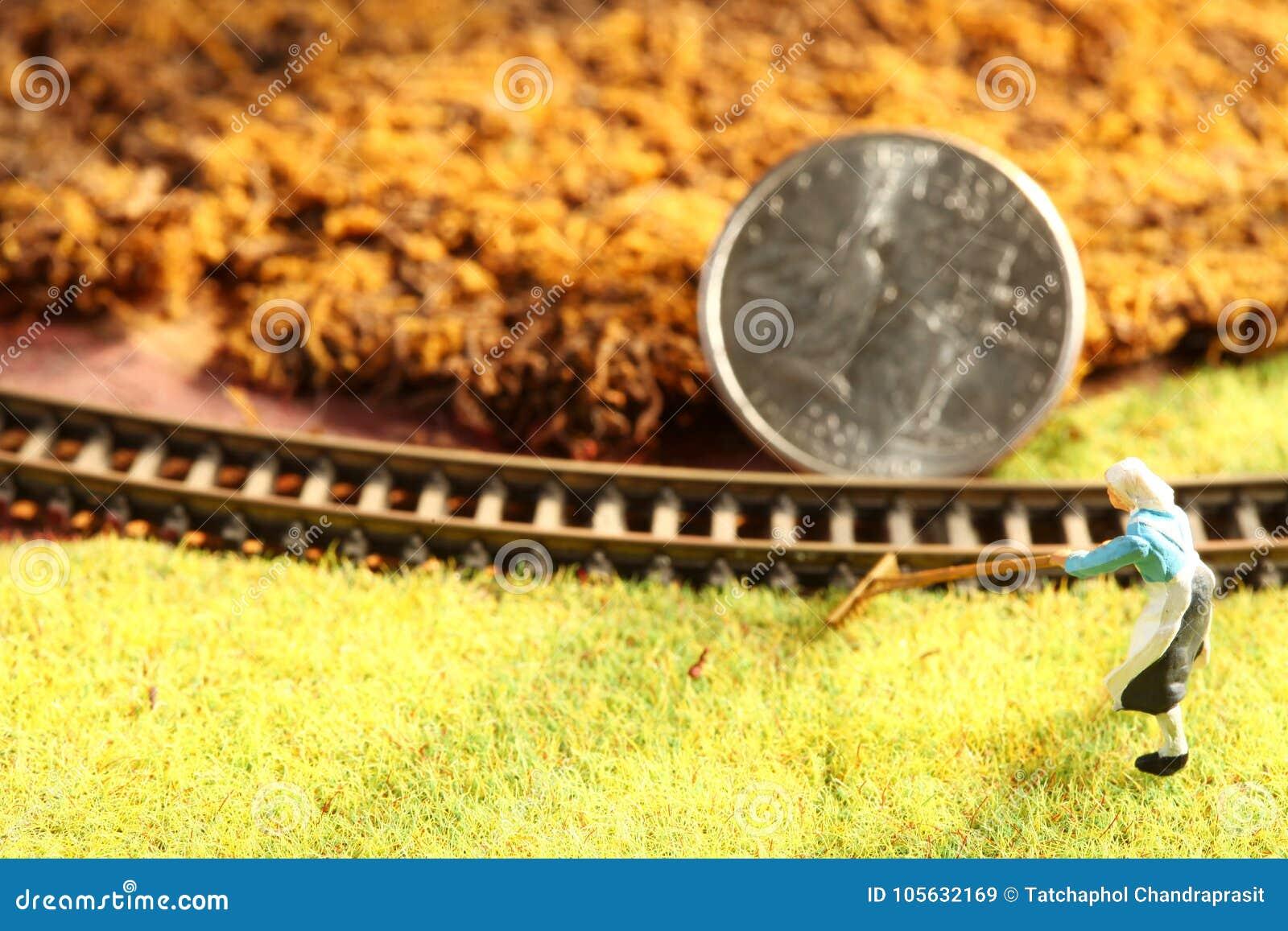 Монетка денег положила дальше миниатюрную сцену железной дороги модели