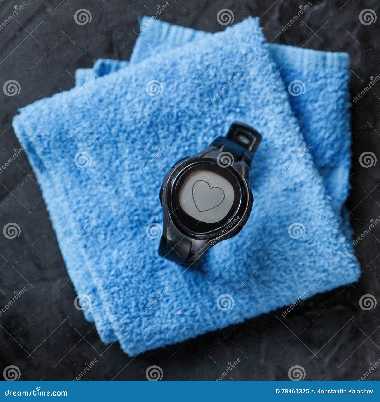 Монитор тарифа сердца на голубом полотенце около футбольного мяча