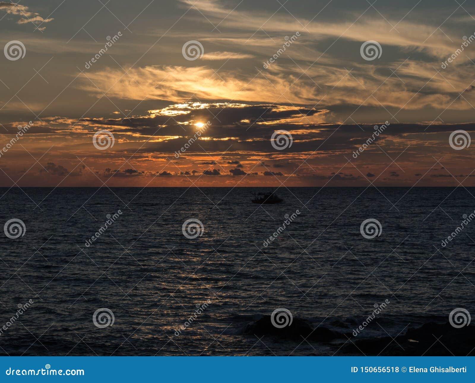 Море и шлюпка на заходе солнца Pantelleria, Сицилия, Италия