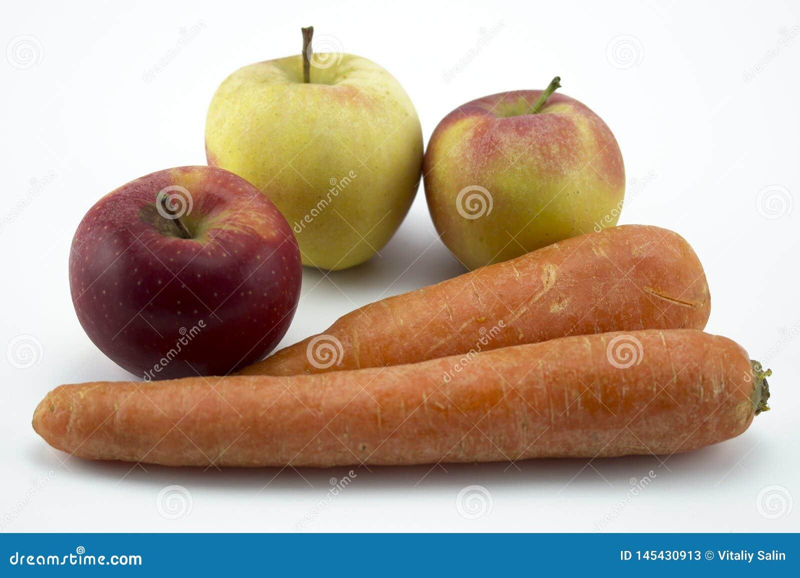 Моркови и яблоки изолированные на белой предпосылке