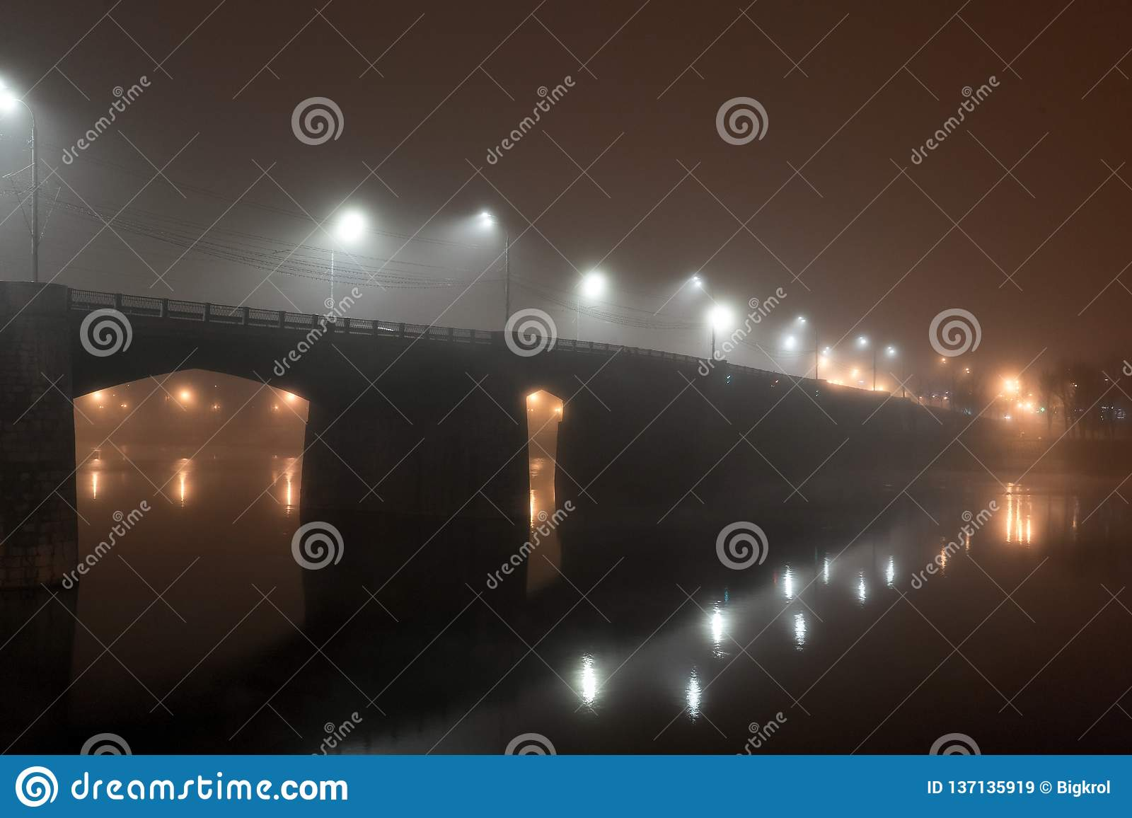 Мост дороги города через реку в густом тумане вечером загоренном фонариками