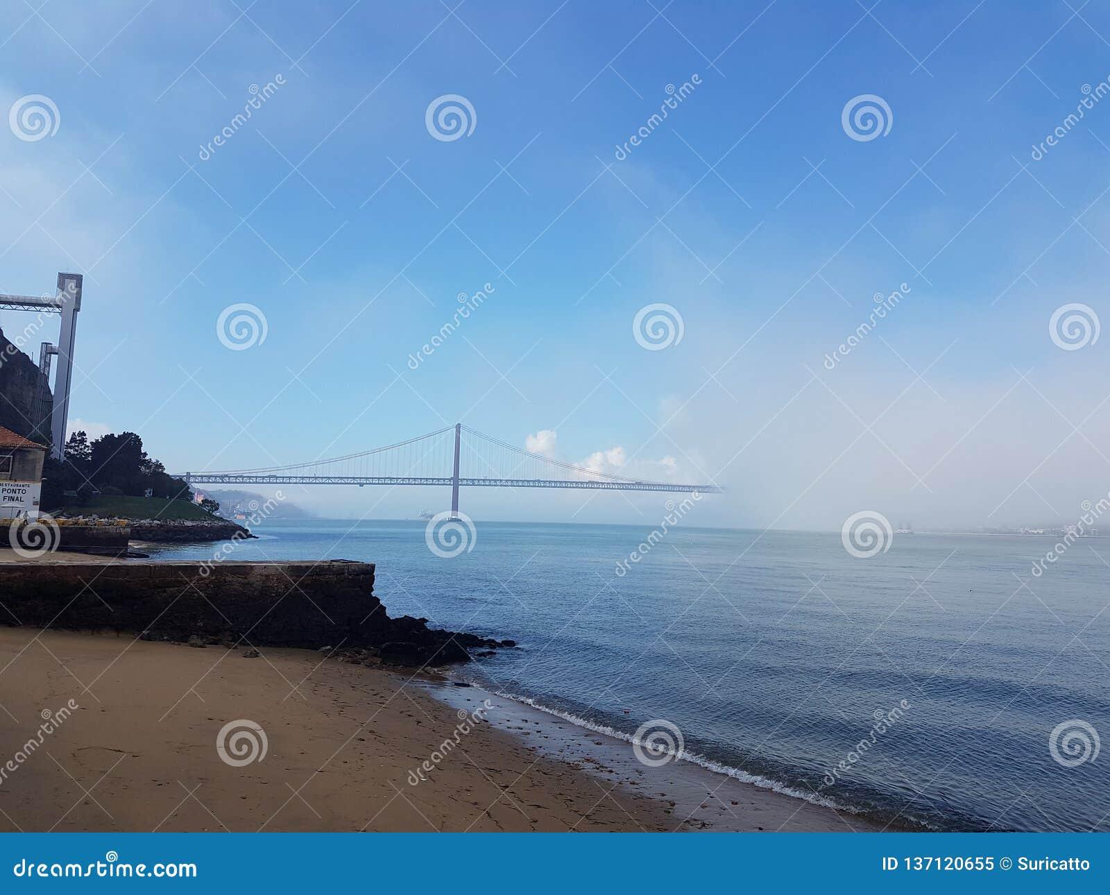 Мост Лиссабона 25-ое апреля освобождаясь после туманного утра