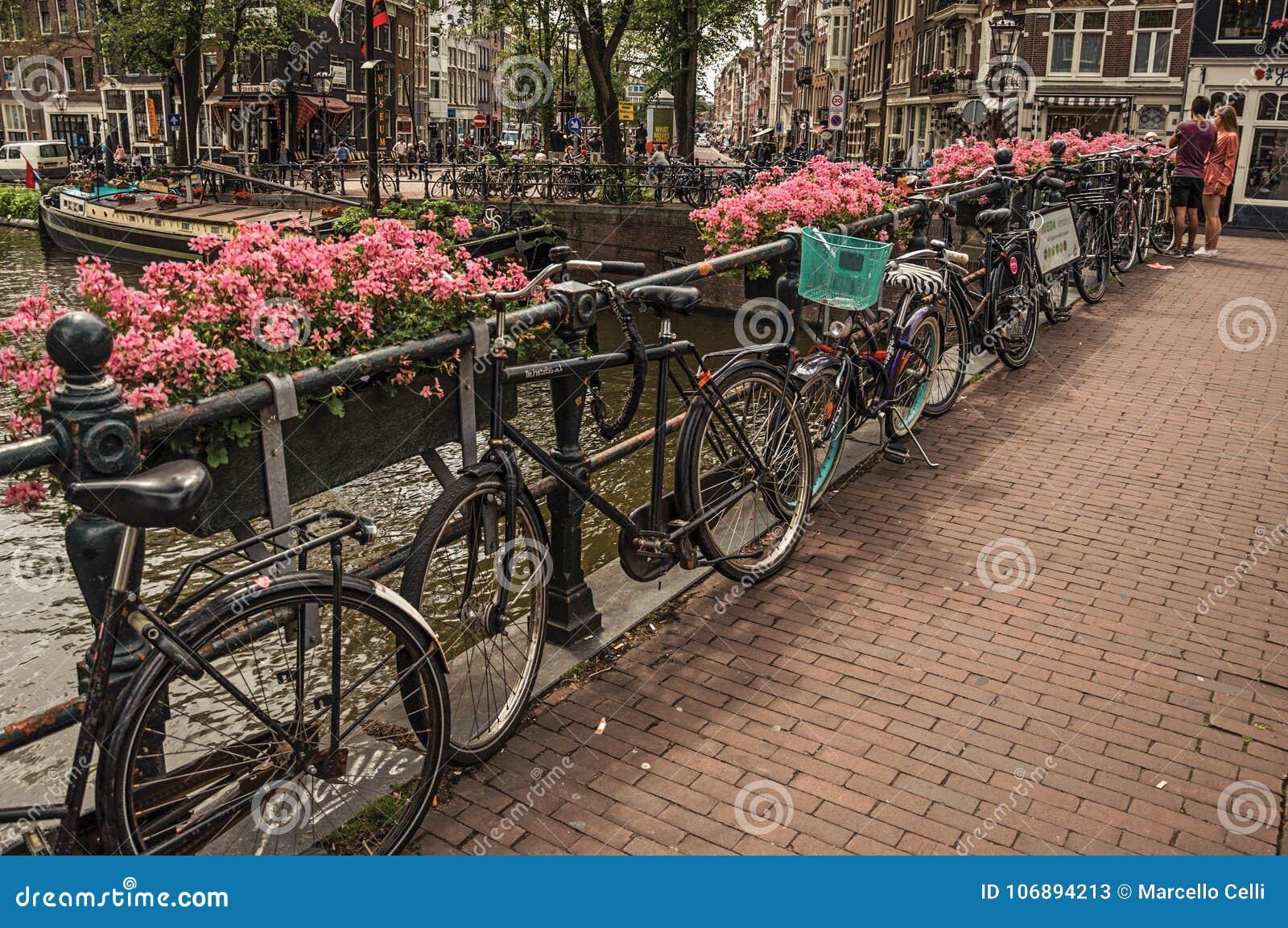 Мост над каналом с цветками, велосипедами, старыми зданиями и людьми в Амстердаме
