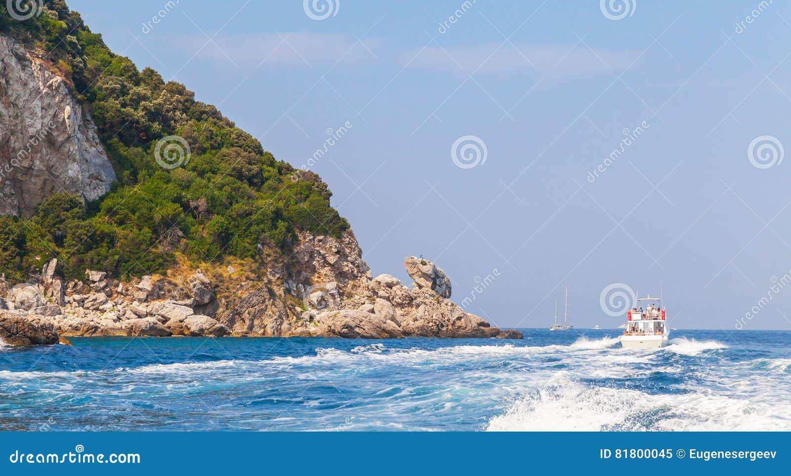 Моторка идет около утесов острова Капри, Италии