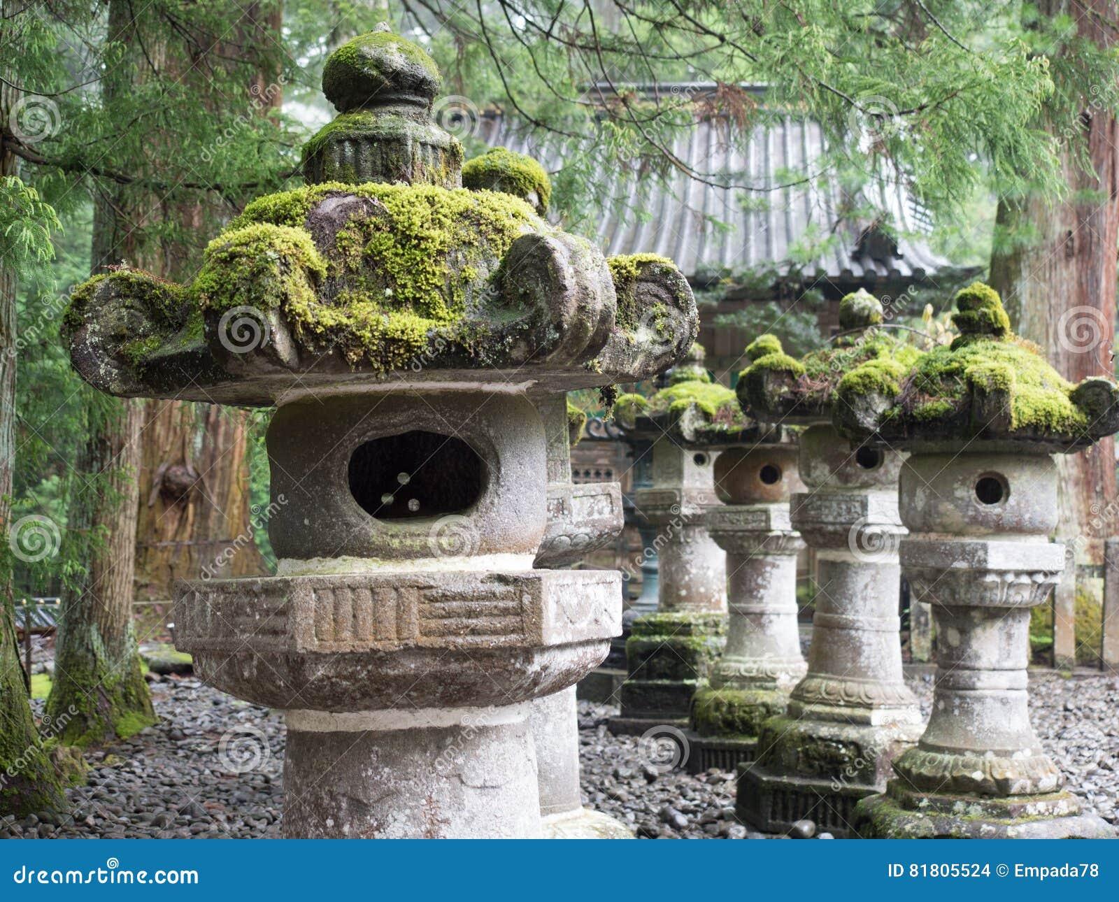 Мох покрыл каменные статуи в саде камешка