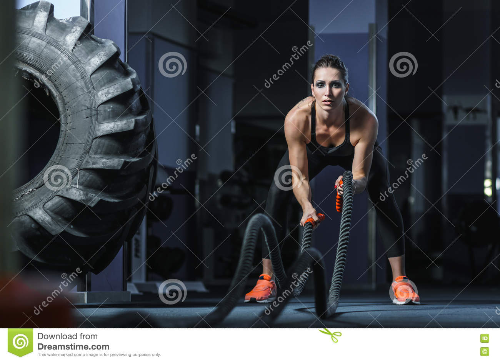 Мощный привлекательный мышечный тренер CrossFit сражает разминку с веревочками
