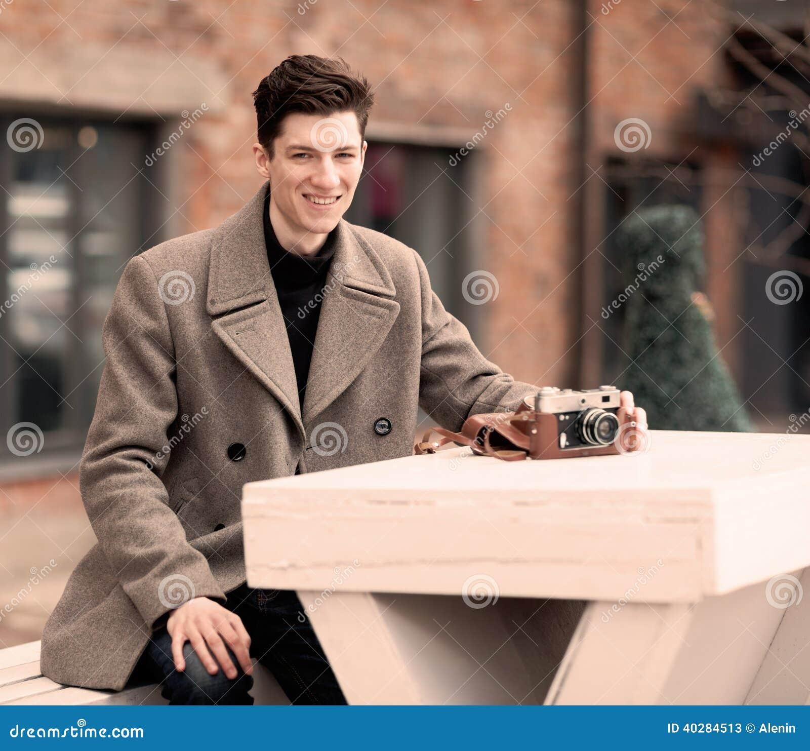 Модель молодого человека в пальто сидит на белой таблице с винтажной камерой outdoors