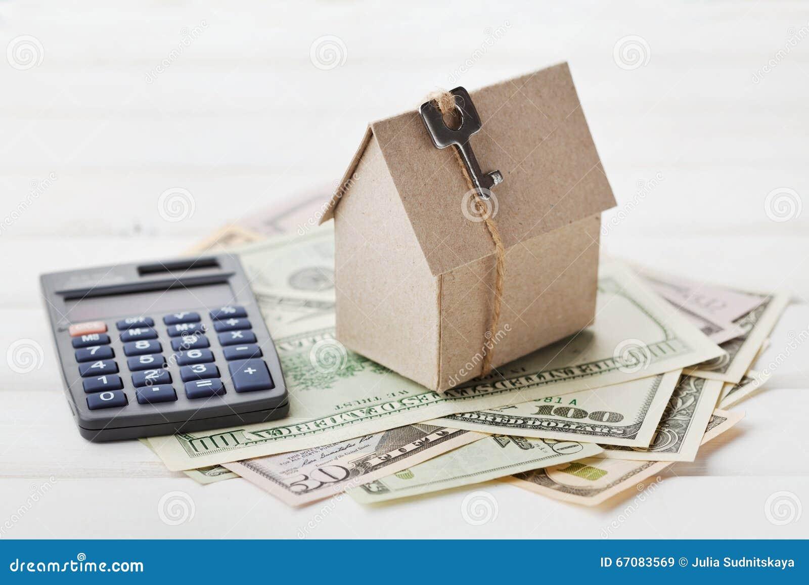 Модель дома картона с ключом, доллары калькулятора и наличных денег Жилищное строительство, заем, недвижимость Цена коммунальных