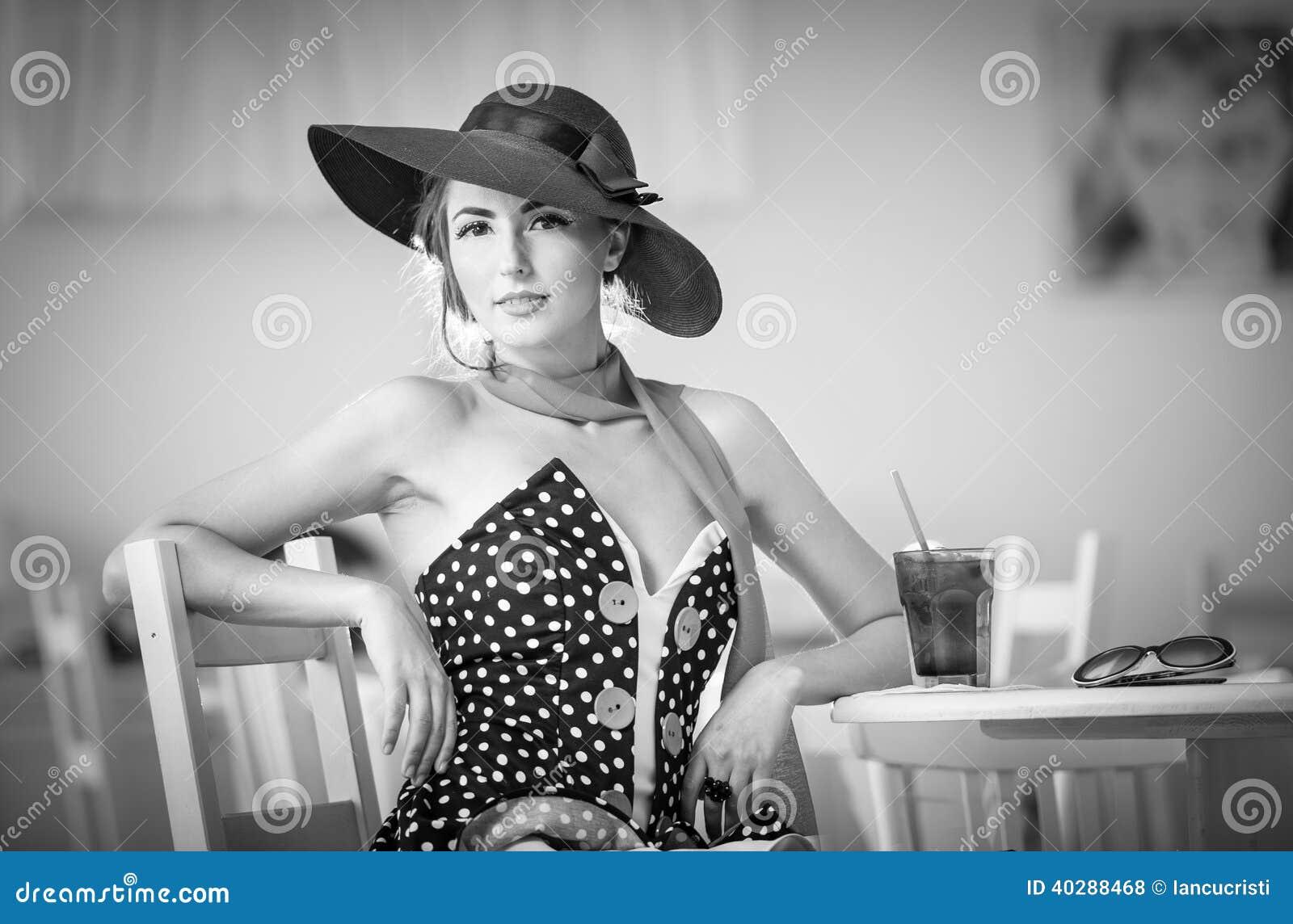 Модная привлекательная дама при шляпа и шарф сидя в ресторане