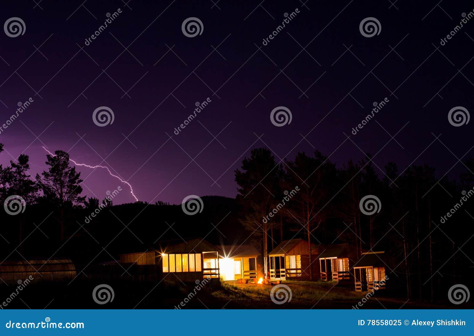 Молния в ночном небе над домами