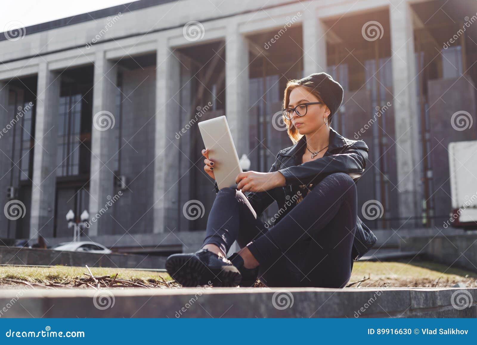 Модно одетая девушка битника в связанной шляпе использует электронную таблетку сидя снаружи в городе