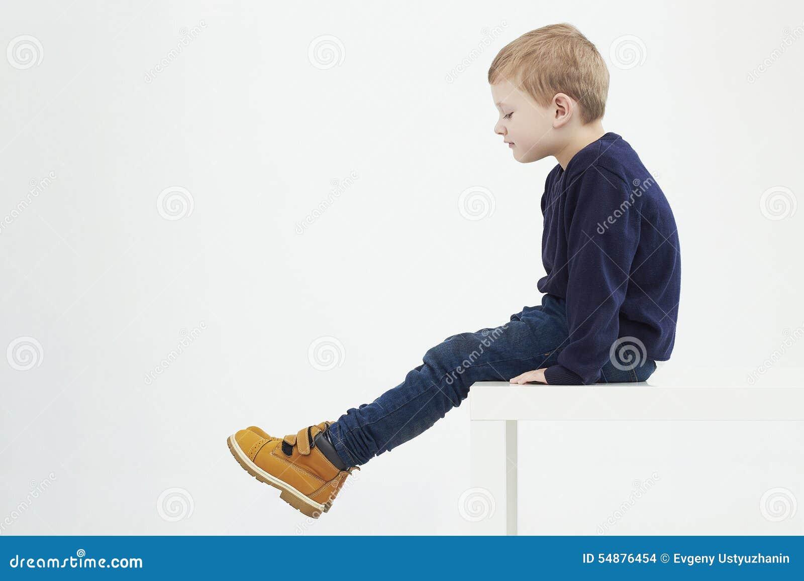 Модный ребенок в желтых ботинках Малыши способа мальчик сидя на таблице
