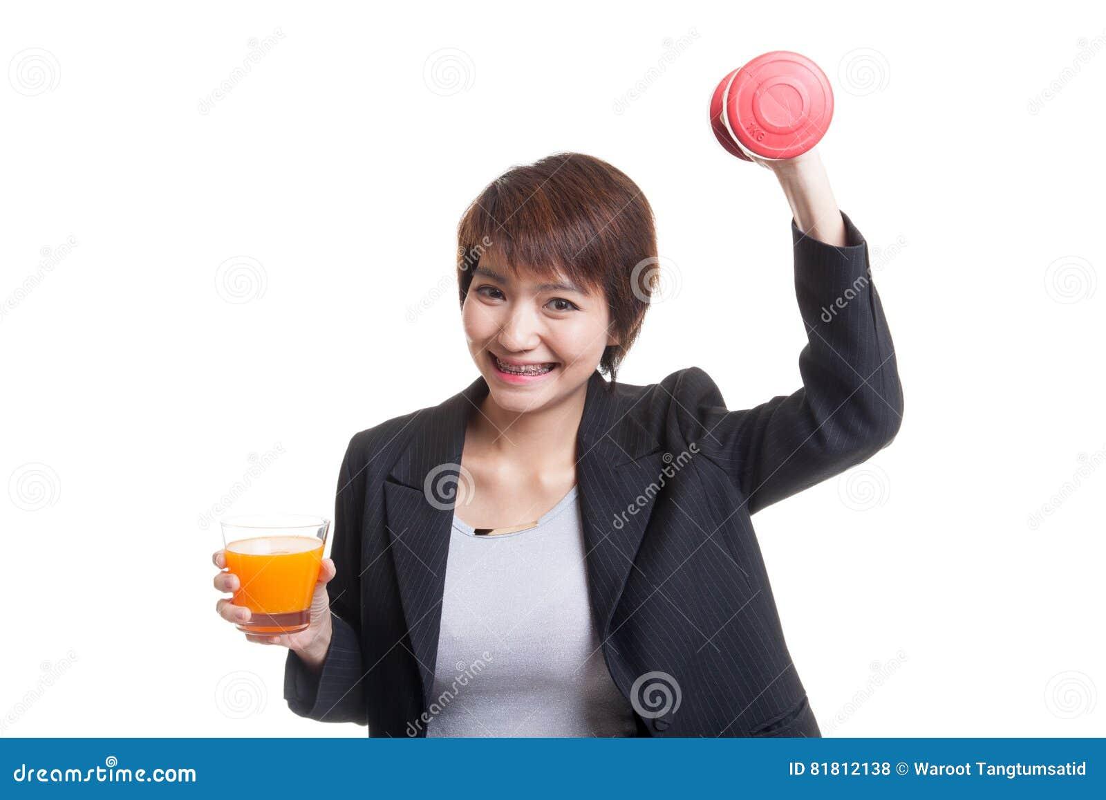 Молодая азиатская женщина с апельсиновым соком питья гантели