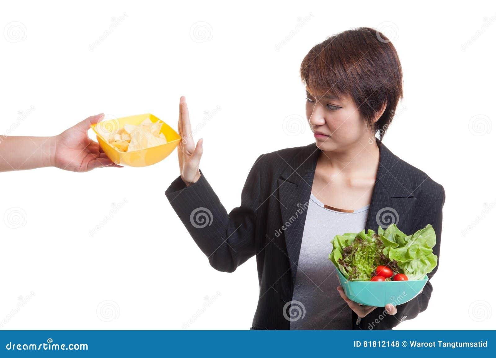 Молодая азиатская женщина с салатом говорит нет к картофельным стружкам