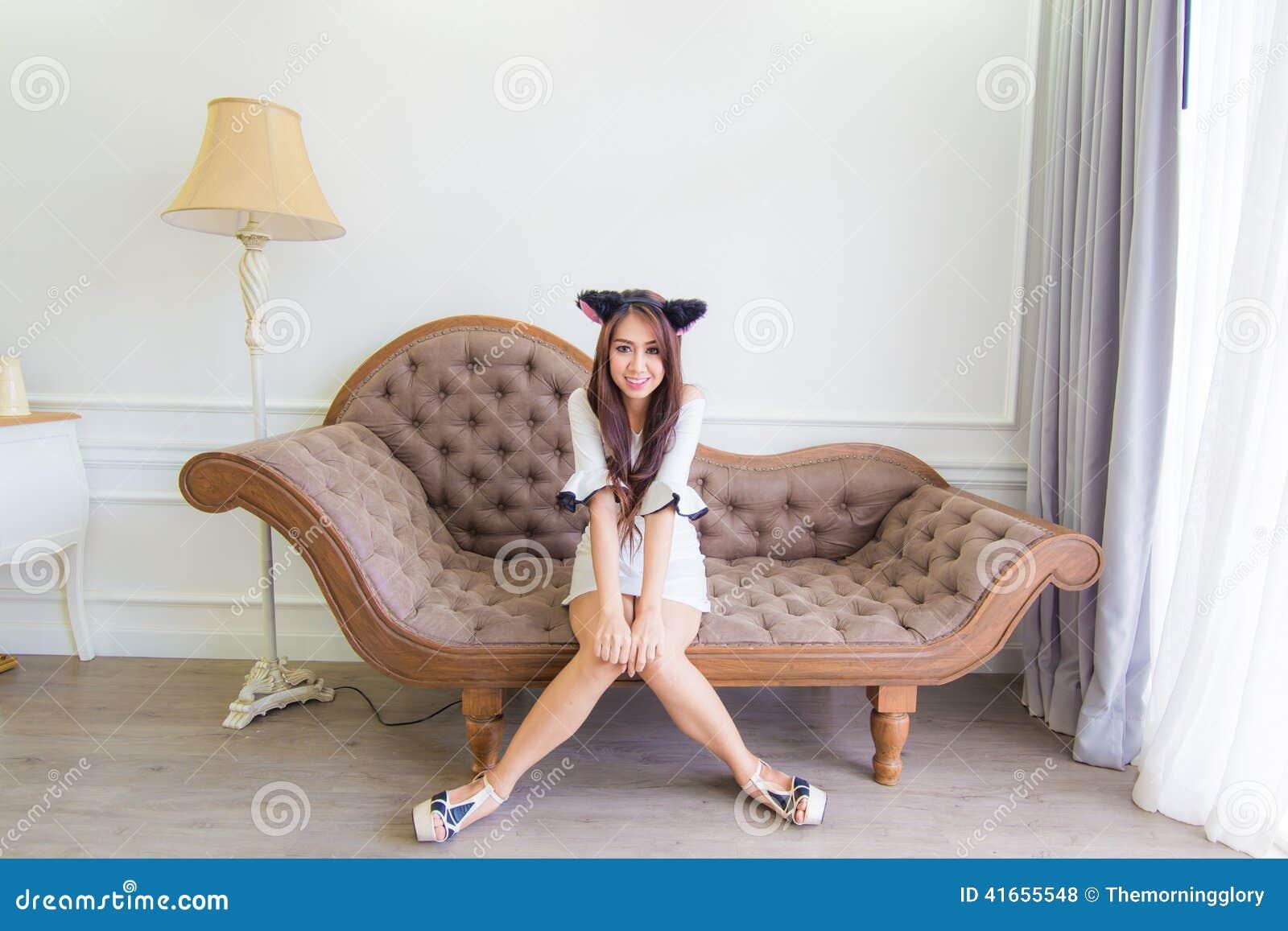 Молодая азиатская женщина улыбки сидя на кресле в современной комнате